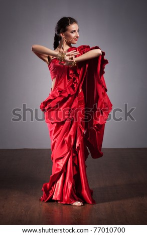 Portrait of Indian dancer in red dress on grey background