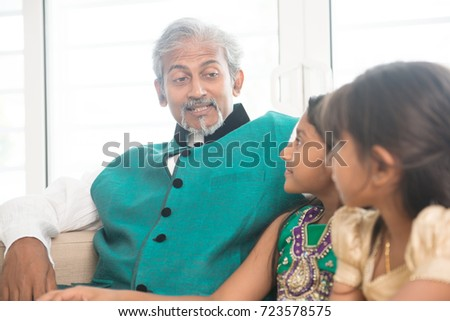 Portrait of Indian family at home. Happy Asian father and children indoors lifestyle.