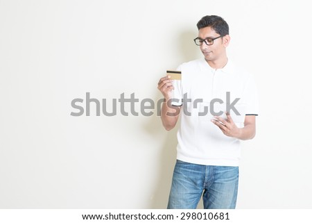 Portrait of Indian guy shopping online using tablet pc, doing transaction by checking credit card. Asian man standing on plain background with shadow and copy space. Handsome male model. - stock photo