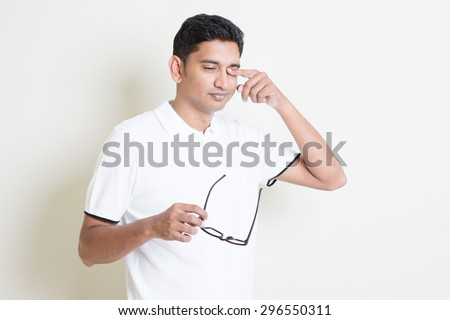 Portrait of Indian guy take off eyeglasses and rubbing his tired eyes. Asian man standing on plain background with shadow and copy space. Handsome male model. - stock photo
