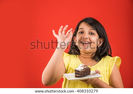 portrait of Indian kid eating cake or pastry, cute little girl eating cake, girl eating chocolate cake over red background - stock photo