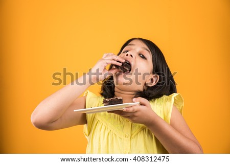 portrait of Indian kid eating cake or pastry, cute little girl eating cake, girl eating chocolate cake or pastry over yellow background - stock photo