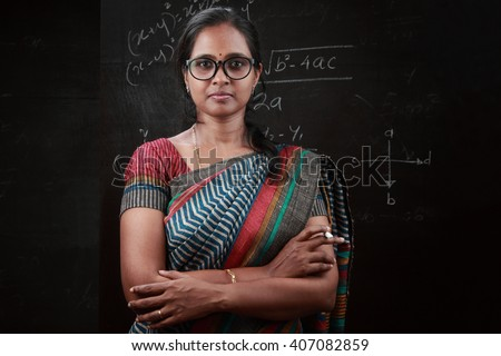 Portrait of Indian lady teacher stands in front of a blackboard - stock photo