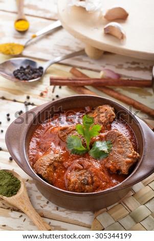 portrait of indian lamb rogan josh served on pot with seasoning - stock photo