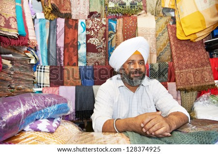 Portrait of Indian sikh man seller in turban with bushy beard at shawl shop - stock photo