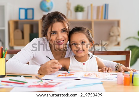 Portrait of Indian woman and her daughter painting together - stock photo