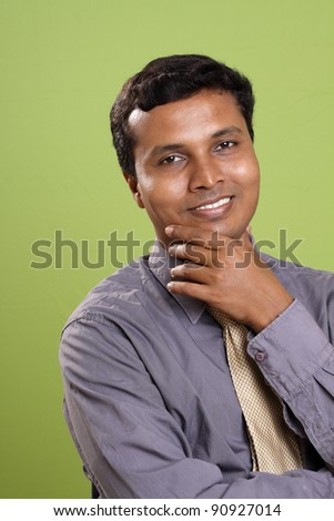 Portrait of indian young businessman on green background. - stock photo