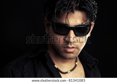 Portrait of Indian young man on black background. - stock photo