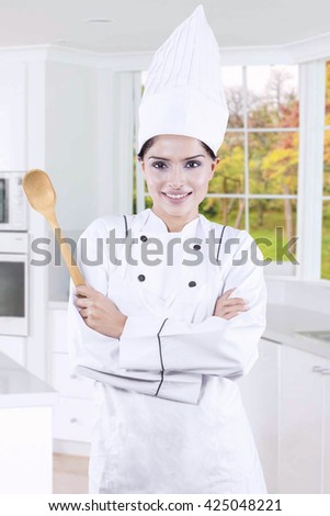 Portrait of indian young woman wearing chef uniform in the kitchen while holding wooden spoon