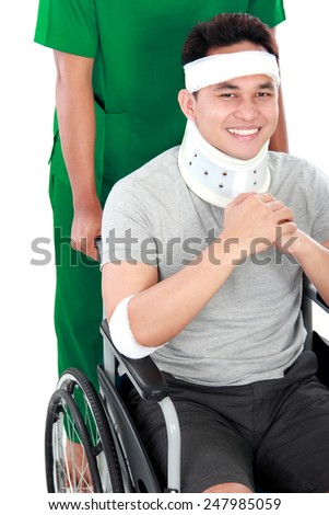 portrait of injured young man in wheelchair help by nurse - stock photo