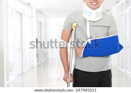 portrait of injured young man use crutch and arm sling - stock photo