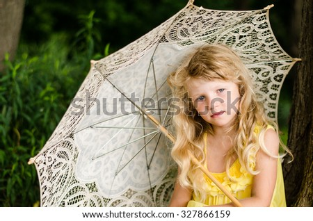 portrait of innocent adorable little child with long blond hair holding lacy sunshade and showing up with her hand - stock photo