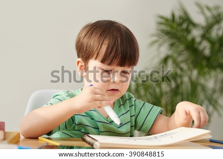 Portrait of inspired kid drawing at his desk - stock photo