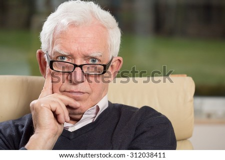 Portrait of intelligent senior man wearing glasses - stock photo