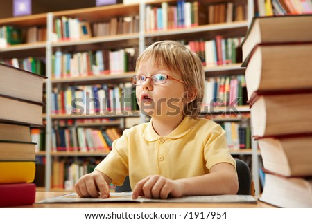 Portrait of interested schoolkid reading book in the library
