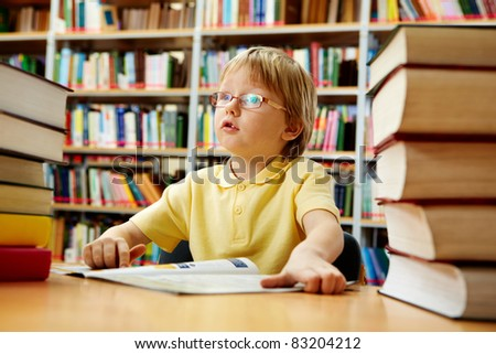 Portrait of interested schoolkid reading book in the library - stock photo
