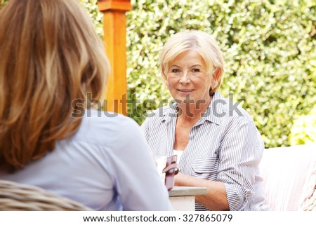 Portrait of investment advisor and senior woman consulting. Businesswoman and elderly female sitting at home in the garden and planning for the future.