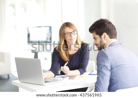 Portrait of investment advisor businesswoman and young financial businessman analyzing data and working on laptop. - stock photo