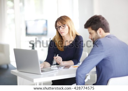 Portrait of investment advisor businesswoman sitting at office in front of computer and consulting with young professional man.  - stock photo