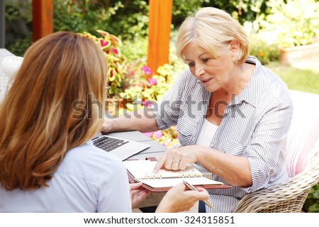 Portrait of investment advisor consulting with retired woman at home. Business adviser and old woman planing the future.  - stock photo