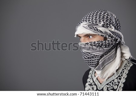 portrait of islamic man in headscarf over grey background - stock photo