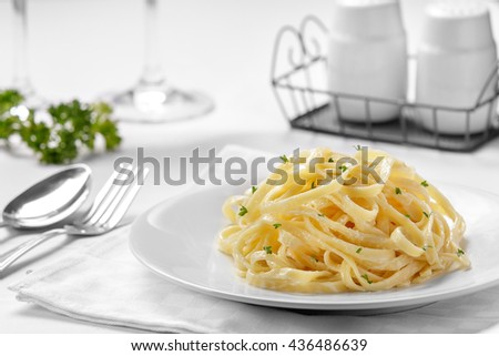 portrait of italian cuisine tagliatelle carbonara on plain white plate - stock photo