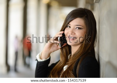 Portrait of japanese business woman in urban background on the phone