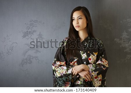 Portrait of Japanese woman in traditional kimono standing by grey wall, looking away.