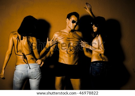 Portrait of jealous people. Handsome man in between two sexy woman - stock photo