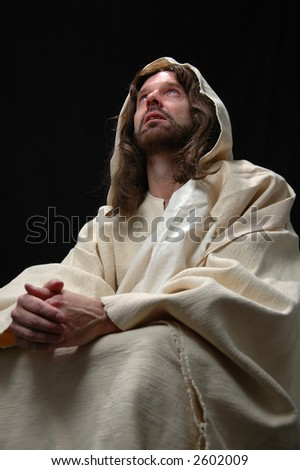 Portrait of Jesus in prayer with black background - stock photo