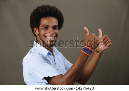 Portrait of joung friendly african american man with thumbs up - stock photo