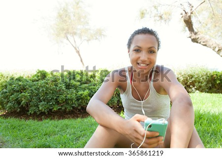 Portrait of joyful african american teenager girl smiling using smartphone and headphones to listen to music, sitting on grass in park, outdoors. Adolescent technology lifestyle, exterior holiday. - stock photo