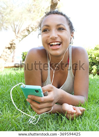 Portrait of joyful african american teenager girl using smartphone and headphones to listen to music, smiling laying on green grass in park, outdoors. Adolescent technology lifestyle, holiday. - stock photo