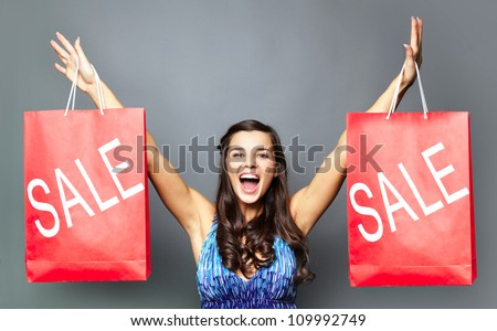 Portrait of joyful brunette with sale paperbags looking at camera - stock photo