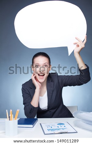 Portrait of joyful businesswoman holding paper speech bubble while sitting at workplace - stock photo