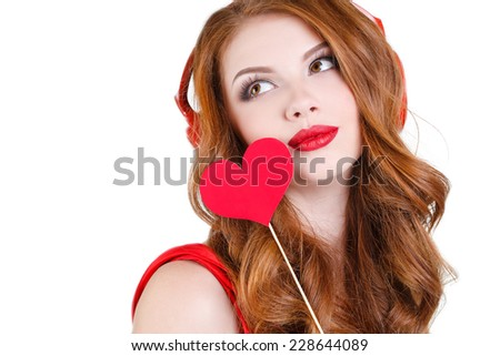 portrait of joyful cheerful cute woman with red hair and red lips holding red hearts in hands in red headphones on head. portrait of attractive woman isolated on white studio shot. Valentine's Day. - stock photo
