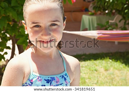 Portrait of joyful child girl having fun in a home garden on a sunny summer holiday, smiling with wet hair and skin outdoors. Active kids lifestyle, swimming costume in house exterior on vacation. - stock photo