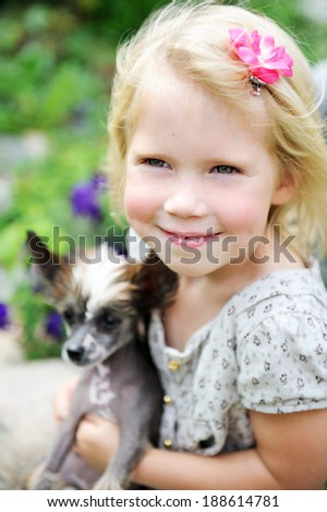 Portrait of joyful child girl with a cute puppy dog - stock photo