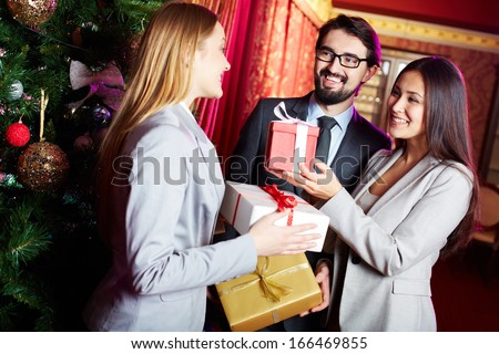 Portrait of joyful colleagues giving xmas presents to each other with xmas tree near by  - stock photo