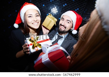 Portrait of joyful colleagues in Santa caps holding Crhistmas gifts in nightclub  - stock photo