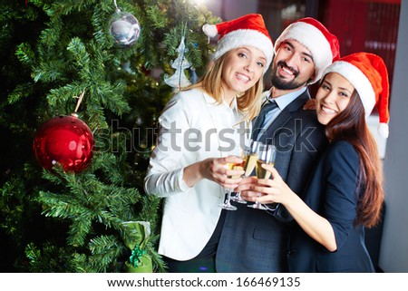 Portrait of joyful colleagues in Santa caps toasting with champagne by Christmas tree  - stock photo