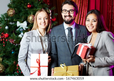 Portrait of joyful colleagues with giftboxes looking at camera with xmas tree on background  - stock photo
