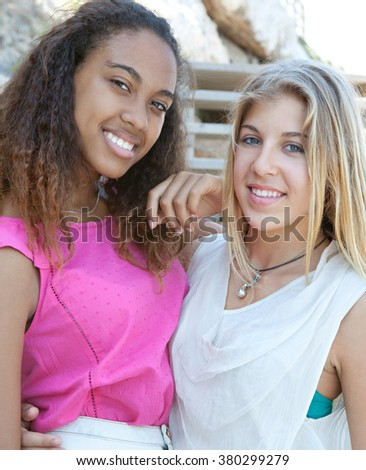 Portrait of joyful diverse teenagers girls friends smiling looking at camera in sunny coastal outdoors. Adolescents travel lifestyle. Young people being close with arms around each other. - stock photo