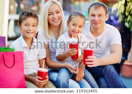 Portrait of joyful family having break and looking at camera in the mall - stock photo