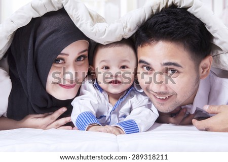 Portrait of joyful family with a baby playing and laughing together on the bed under blanket - stock photo