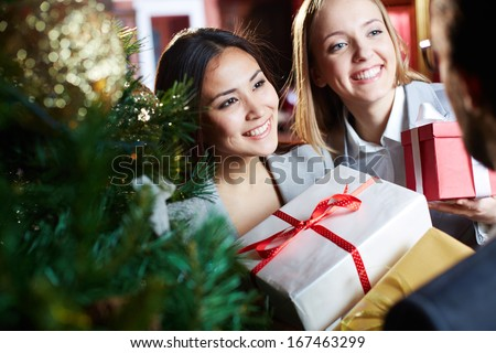 Portrait of joyful females giving xmas presents to their associate - stock photo