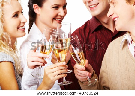 Portrait of joyful friends looking at each other with smiles during pronouncing toast - stock photo