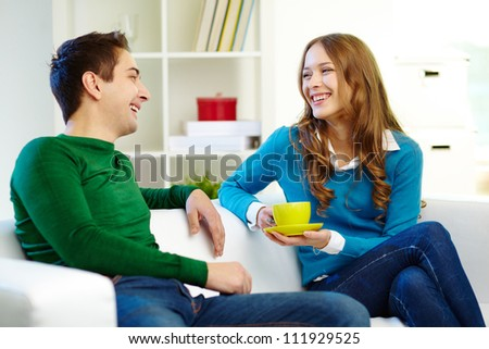 Portrait of joyful friends looking at one another while chatting - stock photo