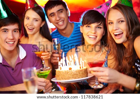 Portrait of joyful friends toasting and looking at camera at birthday party - stock photo