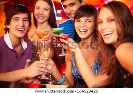 Portrait of joyful friends toasting and looking at camera at party with focus on happy girl and guy